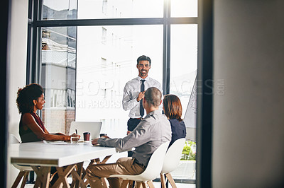 Buy stock photo Shot of a businessman giving a presentation to coworkers in a boardroom meeting