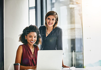 Buy stock photo Portrait of two businesswomen working together on a laptop in an office