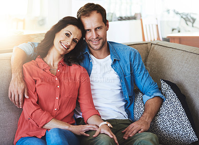 Buy stock photo Cropped portrait of an affectionate couple sitting on the sofa at home