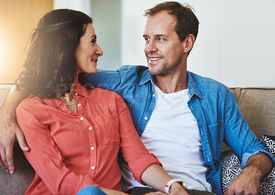 Buy stock photo Cropped shot of an affectionate couple sitting on the sofa at home