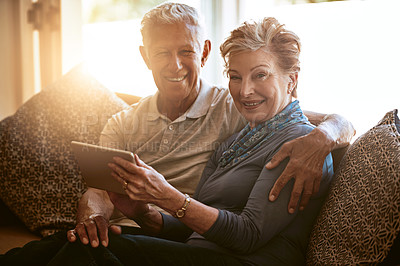 Buy stock photo Portrait of a happy senior couple using a digital tablet together on the sofa at home