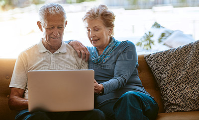 Buy stock photo Shot of a happy senior couple using a laptop together on the sofa at home