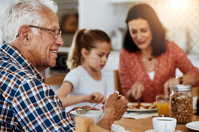 Buy stock photo Cropped shot of an elderly man enjoying breakfast with his family at home