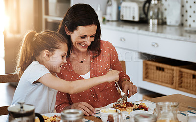 Buy stock photo Cropped shot of a mother and her little daughter having breakfast together at home