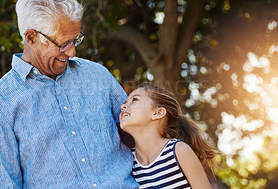Buy stock photo Shot of a cute little girl spending time outside with her grandfather
