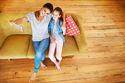 Buy stock photo Shot of a mother and her little daughter taking a selfie together at home