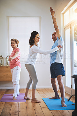 Buy stock photo Shot of a teacher helping a senior man during a yoga class