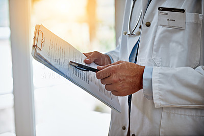 Buy stock photo Closeup shot of a doctor holding a clipboard reading a medical chart