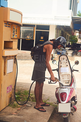 Buy stock photo Shot of a young tourist refueling his scooter at a gas station while exploring a foreign city