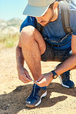 Buy stock photo Shot of a young man tying his shoelaces while out on a hike