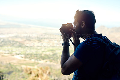 Buy stock photo Rear view shot of a young man taking a photo of the scenic view from the top of a mountain