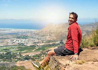 Buy stock photo Portrait of a sporty young man admiring the view from the top of a mountain