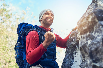 Buy stock photo Shot of a happy young hiker enjoying a mountain trail on his own