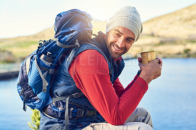 Buy stock photo Shot of a happy hiker drinking coffee while admiring a lake view on a trail