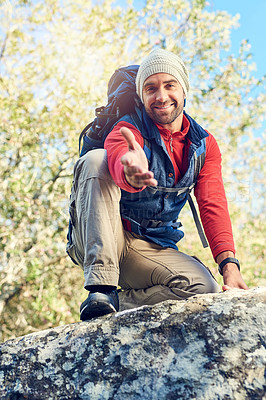 Buy stock photo Portrait of a happy hiker extending his hand while sitting on top of a rock on the trail