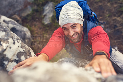 Buy stock photo Shot of a happy hiker climbing over rocks on a mountain trail