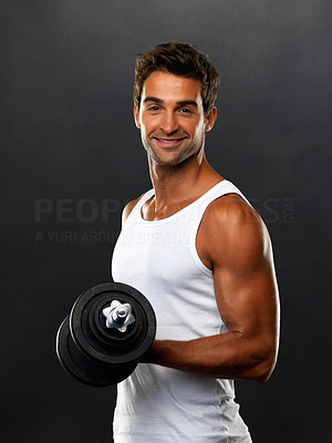 Buy stock photo Portrait of young man lifting weights and smiling on black background