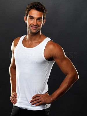 Buy stock photo Portrait of young man in vest standing with hands on hips and smiling against black background