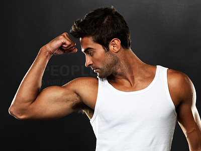 Buy stock photo Handsome muscular man flexing his biceps on black background