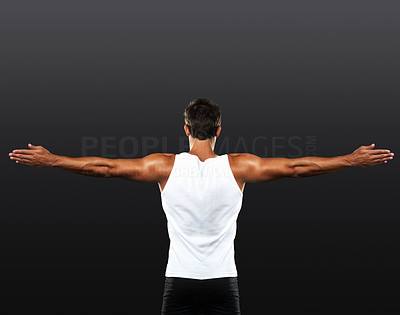 Buy stock photo Rear view of muscular man stretching his arms on black background