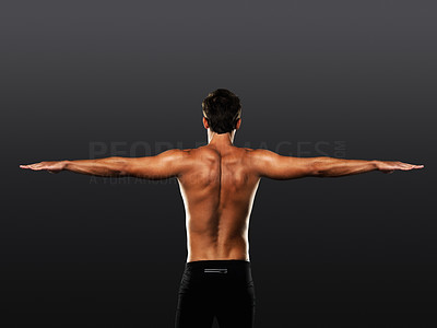 Buy stock photo Rear view of man stretching his arms on black background
