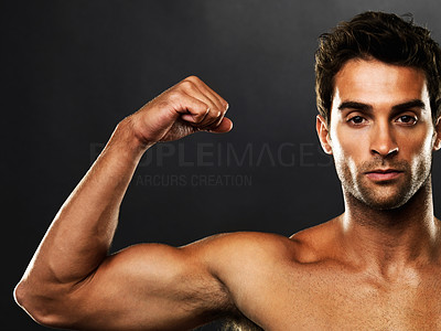 Buy stock photo Closeup portrait of confident muscular man flexing his biceps on black background