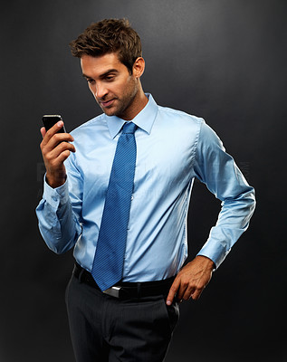 Buy stock photo Young business man standing on black background reading a text message