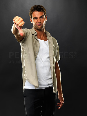 Buy stock photo Portrait of young man standing on black background and giving you a thumbs down