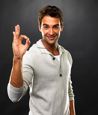 Buy stock photo Portrait of man smiling and showing you OK sign on black background