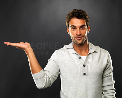 Buy stock photo Portrait of young man holding out his palm and showing you copyspace on black background
