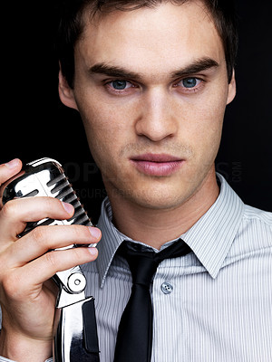 Buy stock photo Portrait of a young male jazz singer holding old fashioned microphone against black background