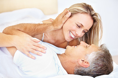 Buy stock photo Closeup of mature couple lying in bed and smiling with man touching woman's face
