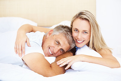 Buy stock photo Portrait of mature couple lying down in their bed at home