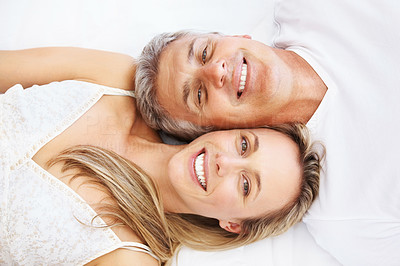 Buy stock photo Top view of a mature couple lying head to head in bed