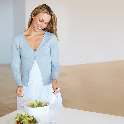 Buy stock photo Portrait of good looking woman preparing a healthy meal of salad in her kitchen at home