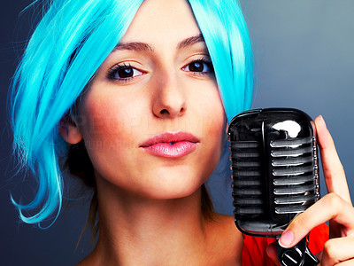 Buy stock photo A beautiful young female pop singer sporting blue hair holding an old fashioned microphone