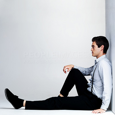 Buy stock photo Portrait of a relaxed young man sitting on the floor against grey background