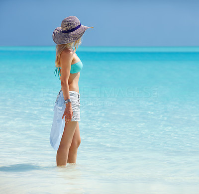 Buy stock photo Portrait of a beautiful young female standing in the water at beach and looking away