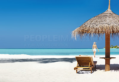 Buy stock photo Panoramic image of exotic tropical beach with relaxing chairs under umbrella and a woman walking in background
