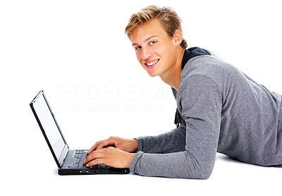 Buy stock photo Studio shot of a young man lying on his stomach and using a laptop