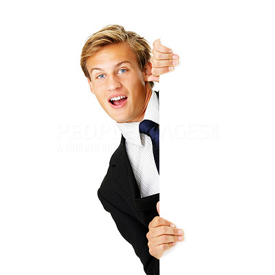 Buy stock photo Studio shot of a young businessman peering from behind a blank placard isolated on white