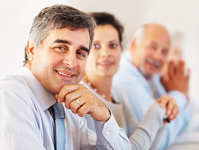Buy stock photo Closeup of smiling business man with colleagues in the background