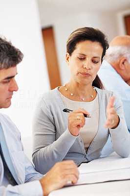 Buy stock photo Mature female executive writing during business meeting