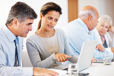 Buy stock photo Mature business associates working on project using laptop with senior associates in the background
