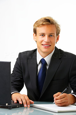 Buy stock photo Studio shot of a young businessman sitting at his desk isolated on white