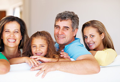 Buy stock photo Family portrait of mature parents with their daughters sitting on sofa
