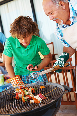 Buy stock photo Grand father teaching his grand son to barbeque food