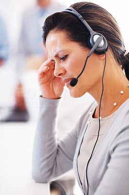 Buy stock photo Stressed or tired call centre operator with a headache, grimacing and touching her head - copyspace