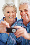 Smiling old couple taking a photo on mobile phone