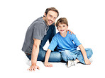 Handsome young man sitting with his son smiling